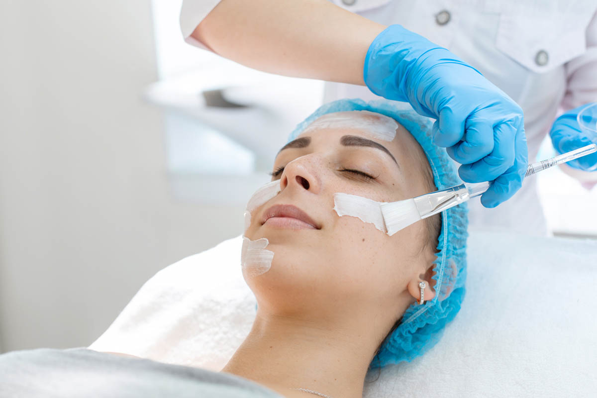 Cosmetologist applies cream on the patient's face